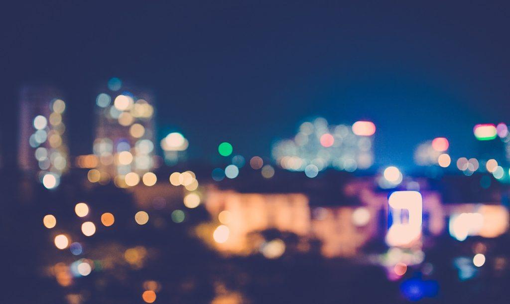 Photo nocturne d'une ville dont on aperçoit les lumières floues.